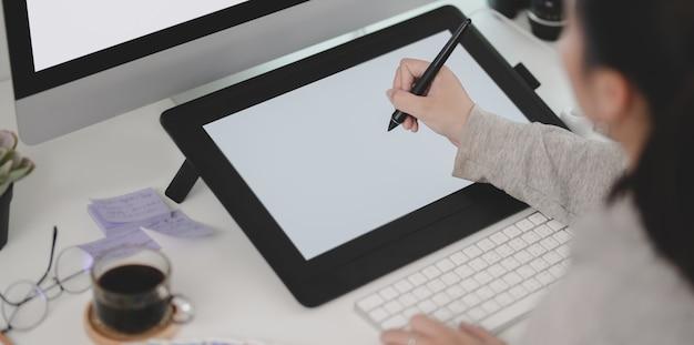 Close-upmening van jonge vrouwelijke ontwerper die aan haar project werken terwijl het gebruiken van tablet