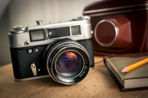 Close-upmening van klassieke filmcamera en notitieboekje op houten bureau