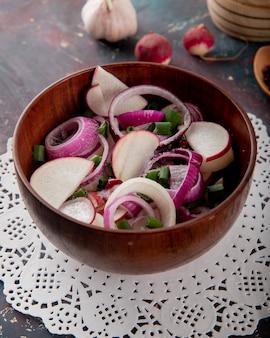 Close-upmening van kom plantaardige salade met de lente-ui van de radijsui op document kleedje op kastanjebruine achtergrond