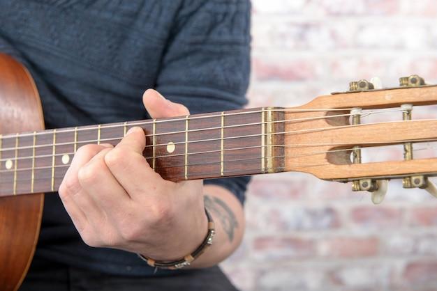 Close-upmening van man hand het spelen gitaar