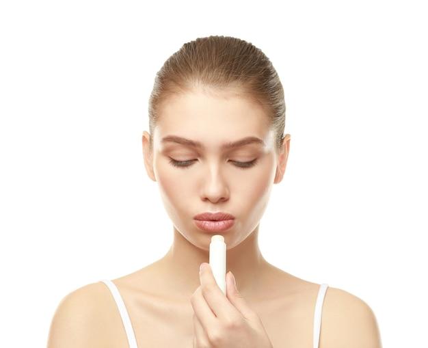 Close-upmening van mooie jonge vrouw die lippenstift, witte muur toepast