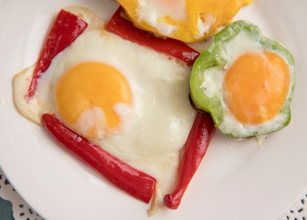 Close-upmening van ontbijt vastgestelde plaat met peper en ei op document kleedje