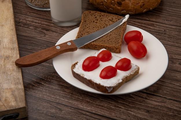 Close-upmening van plaat van de plakken van het roggebrood die met kwark en tomaten en mes op houten achtergrond worden gesmeerd