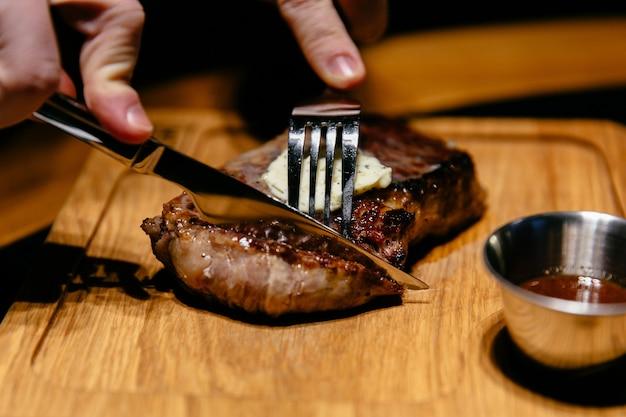Close-upmening van smakelijk lapje vlees met saus. de handen van man beginnen een snee te snijden.