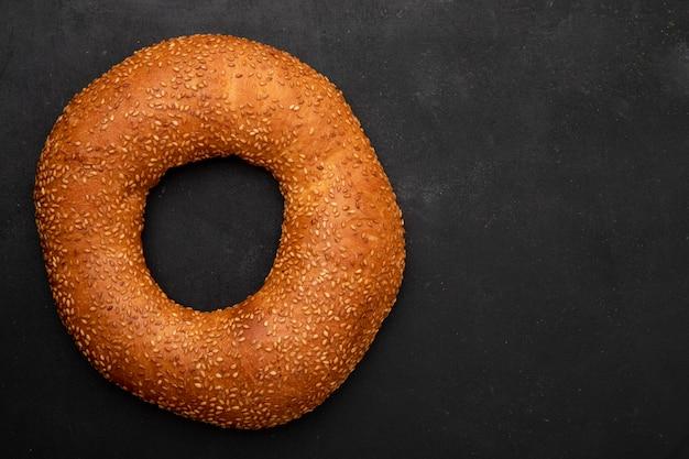 Close-upmening van turks sesamongezuurde broodje aan linkerkant en zwarte achtergrond met exemplaarruimte