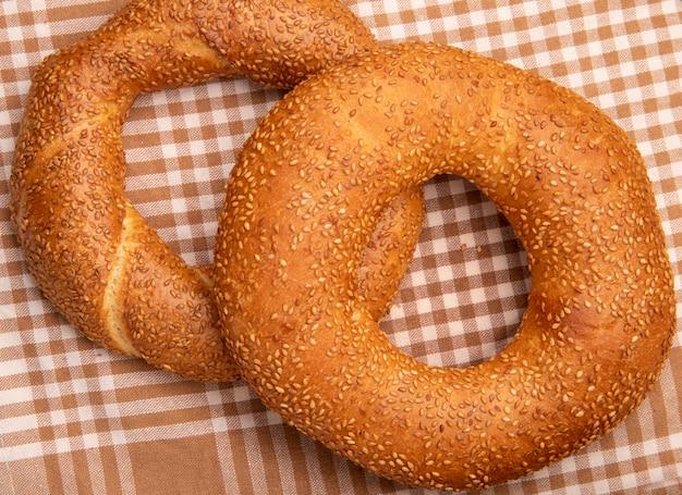 Close-upmening van turkse sesamongezuurde broodjes op de achtergrond van de plaiddoek