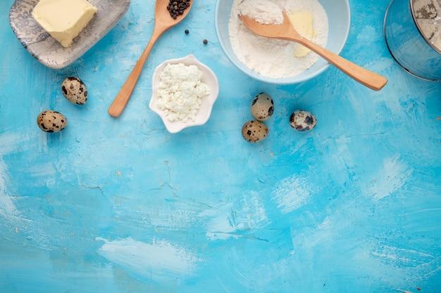 Close-upmening van voedsel als het meelboter van het kwarkei met zwarte peper op blauwe achtergrond met exemplaarruimte