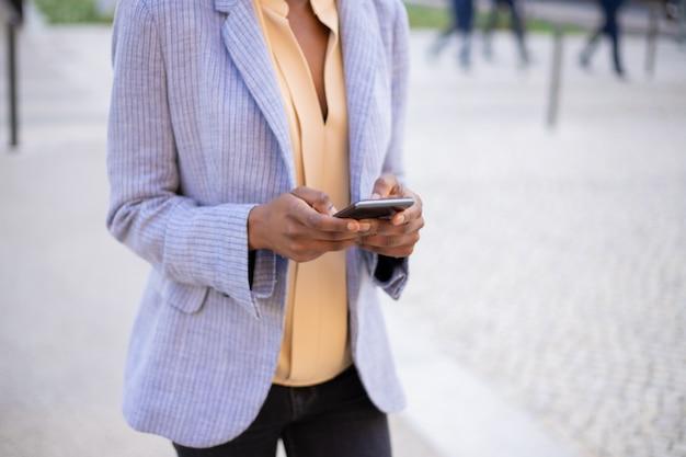 Close-upmening van vrouwelijke handen die moderne telefoon op straat met behulp van
