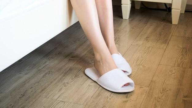 Close-upmening van vrouwelijke voeten in witte pantoffels op houten vloer bij slaapkamer