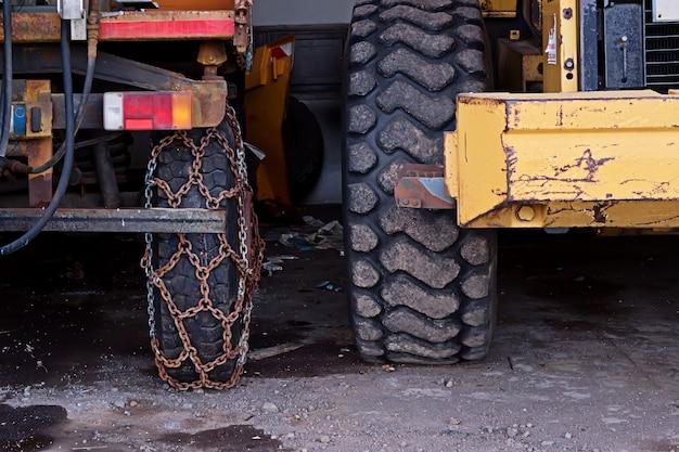 Close-upmening van wiel van vrachtwagen met roestige veiligheidskettingen op weg