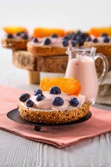 Close-upmening van zoete broodjes met yoghurt, bosbes en plak van dadelpruim op witte houten lijst