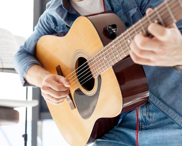 Close-upmens die een akoestische gitaar houden
