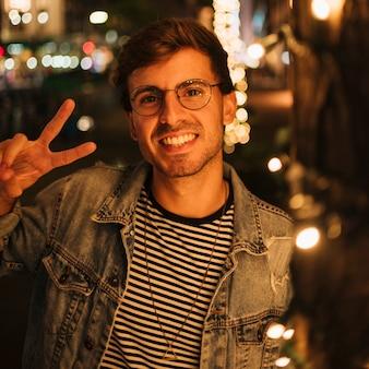 Close-upmens die vredesteken en glimlach maken