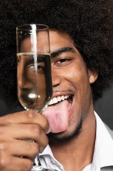 Close-upmens die zijn gezicht behandelen met een glas champagne