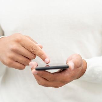 Close-upmens die zijn mobiele telefoon doorbladeren