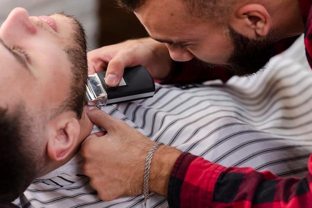 Close-upmens in kapperswinkel het scheren