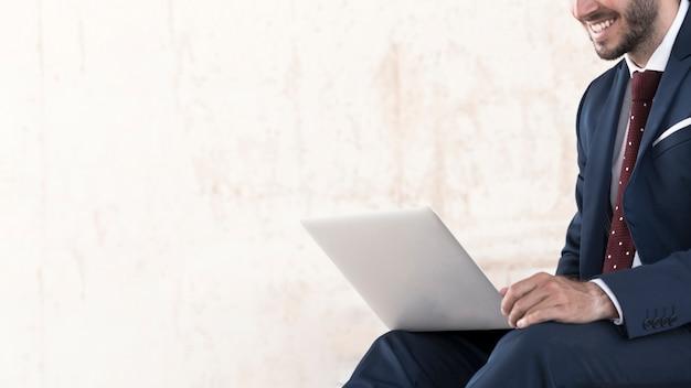 Close-upmens in kostuum die aan laptop werken