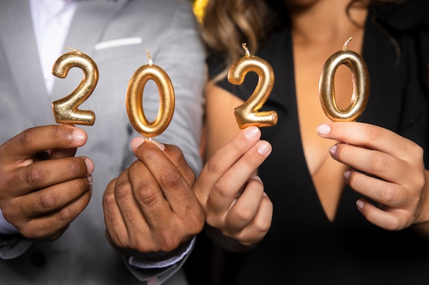 Close-upmensen die kaarsen met nieuw jaar 2020 houden