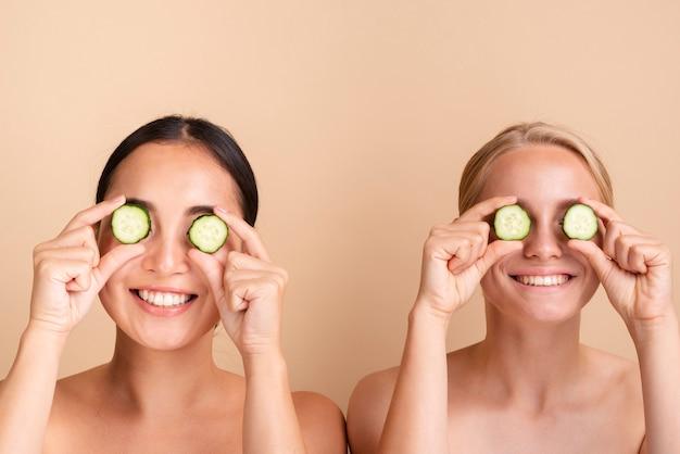 Close-upmodellen die met komkommerplakken stellen