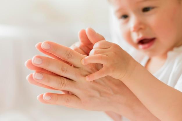 Close-upmoeder en baby het spelen met handen