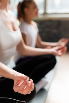 Close-upmoeder en dochter die op matten in gymnastiek mediteren