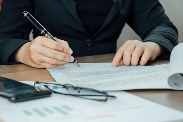 Close-uponderneemster die termijnen en overeenkomstdocument op haar bureau ondertekenen