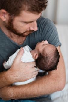Close-upouder die zijn baby houdt