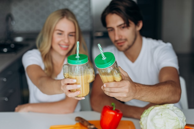 Close-uppaar die een glas met smoothies rasing. concept gezond voedsel.