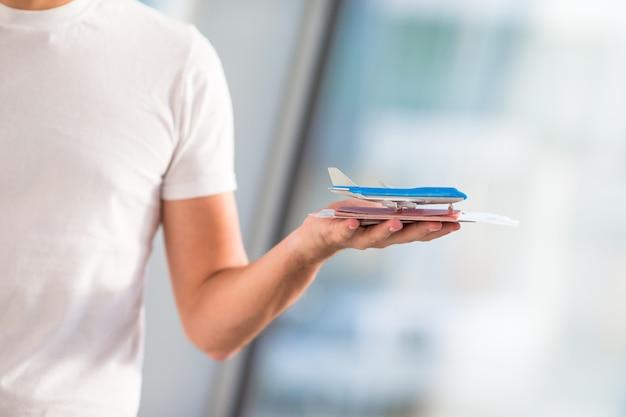 Close-uppaspoorten en instapkaart bij luchthaven binnen achtergrondvliegtuig
