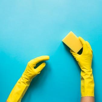 Close-uppersoon die met handschoenen spons houdt