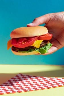 Close-uppersoon die smakelijke cheeseburger steunt