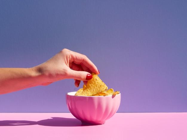 Close-uppersoon die tortilla uit een roze kom nemen