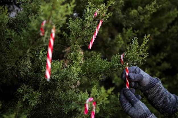Close-uppersoon met handschoenen die de kerstmisboom verfraaien