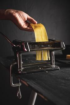 Close-uppersoon met pastamachine en deeg