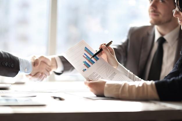 Close upplanning van financiële ontwikkeling en handdruk van zakenpartners