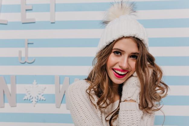 Close-upportret binnenshuis van meisje met wijd open blauwe ogen en sneeuwwitte glimlach. jong model in witte warme muts poseert gelukkig op gestreepte muur