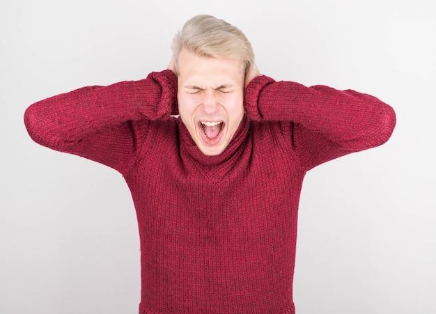 Close-upportret dat van de jonge boze ongelukkige beklemtoonde mens zijn oren behandelt, zijn ogen sluit om te zeggen stop makend dat luide die lawaai, op witte muur wordt geïsoleerd. negatieve emotie