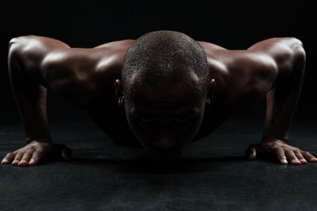 Close-upportret die van de mens van afro amerikaanse sporten, opdrukoefening doen