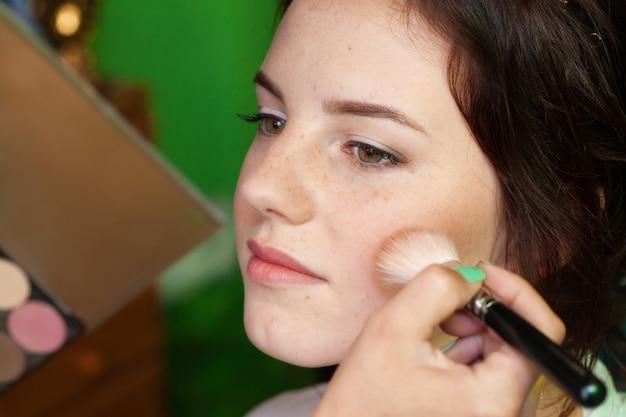 Close-upportret die van een vrouw, make-up met borstel zetten