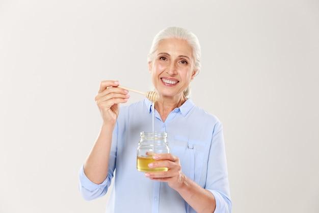 Close-upportret die van glimlachende oude vrouw, honingskruik met lepel houden