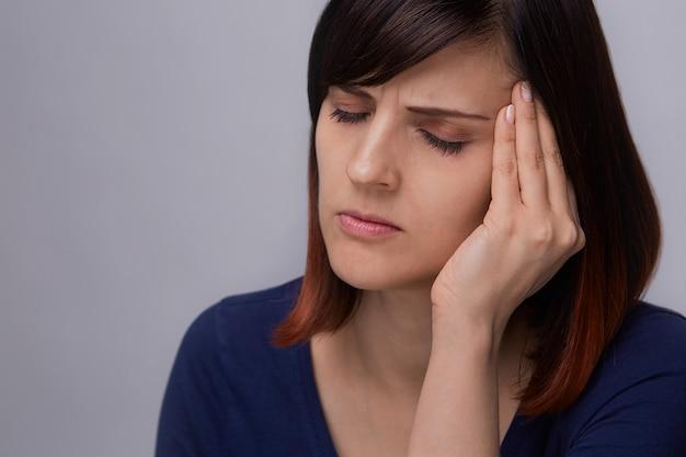Close-upportret die van jonge vrouw aan tandpijn lijden, vingers houden aan kaak en ogen sluiten van pijn.