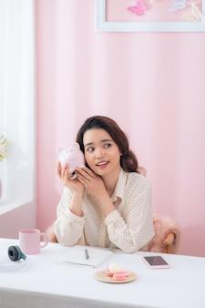 Close-upportret gelukkige, glimlachende bedrijfsvrouw, die roze spaarvarken houdt