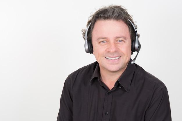 Close-upportret, mannelijke, knappe vertegenwoordiger van de klantenservice, call centrearbeider, exploitant, ondersteunend personeel dat met hoofdtelefoon spreekt