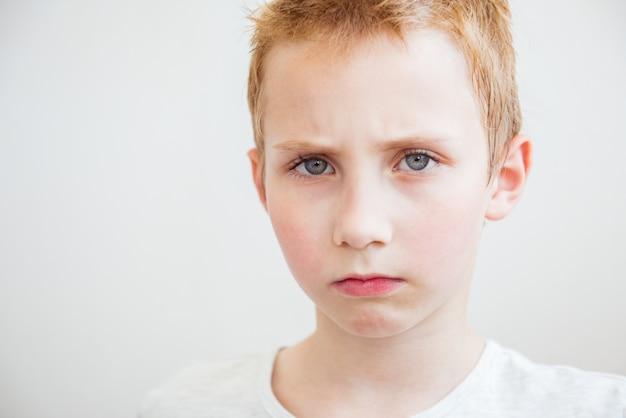 Close-upportret ontevreden pissig boze knorrige pessimistische jongen. negatieve gevoelens van menselijke emoties, gezichtsuitdrukkingen