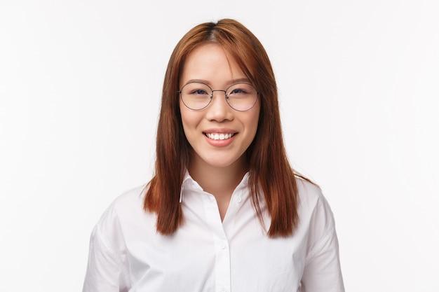 Close-upportret succesvolle glimlachende jonge aziatische vrouw in glazen, die camera bekijken, die gelukkige emoties, vriendelijke houding, gezicht van de beleefde dame van het klantenondersteuningsbureau tonen,