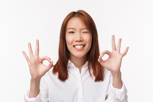 Close-upportret tevreden aziatisch mooi meisje zegt geen probleem, garandeert kwaliteit van product, knipoog verzekert en lacht met tevreden uitdrukking, maakt goed gebaar, zeer goed