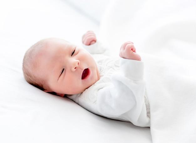 Close-upportret van aanbiddelijk pasgeboren babymeisje die wit kostuum dragen dat in het bed met open mond ligt. leuk babykind dat thuis rust