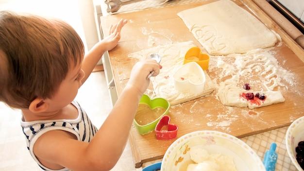 Close-upportret van aanbiddelijke 3 jaar oude peuterjongen die tarwedeeg met deegroller rolt en koekjes met speciaal bedacht plastic mes snijdt. chuld bakken en koken op keuken