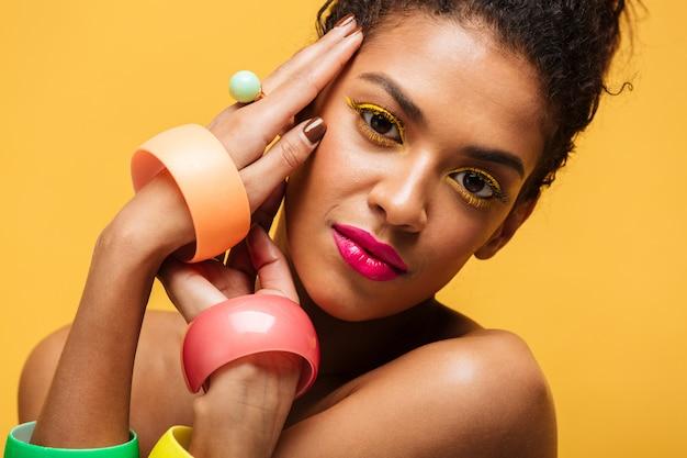 Close-upportret van aanbiddelijke mulatvrouw met gele oogleden en roze lippen die die op cameraholdingshanden gezicht bekijken, over muur wordt geïsoleerd