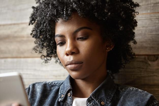Close-upportret van aantrekkelijk afrikaans-amerikaans meisje met krullend haar en perfect gezonde huid